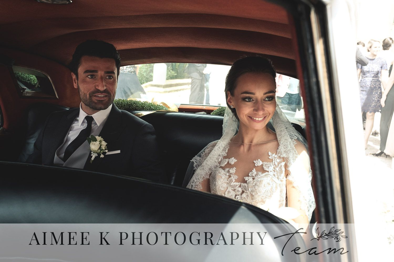 Novios sonrientes en interior de coche blanco tras boda en Mallorca