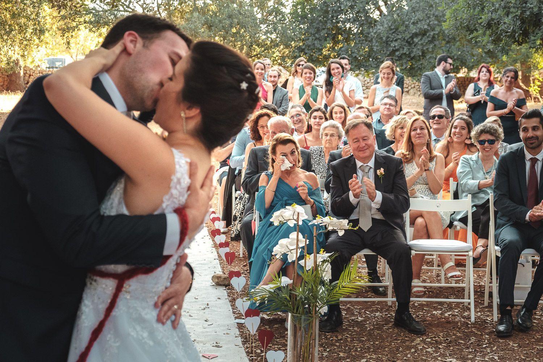 Novios besándose en ceremonia de boda. Invitados emocionados. Mujer llorando. Aplausos.