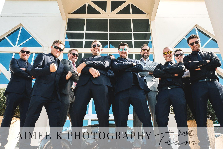 Novio y padrinos. Hombres con traje negro y gafas de sol. Boda en Mallorca.
