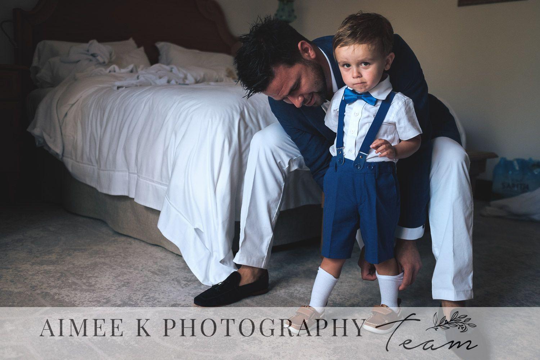 Hombre con traje arregla calcetines a niño pequeño con pajarita.