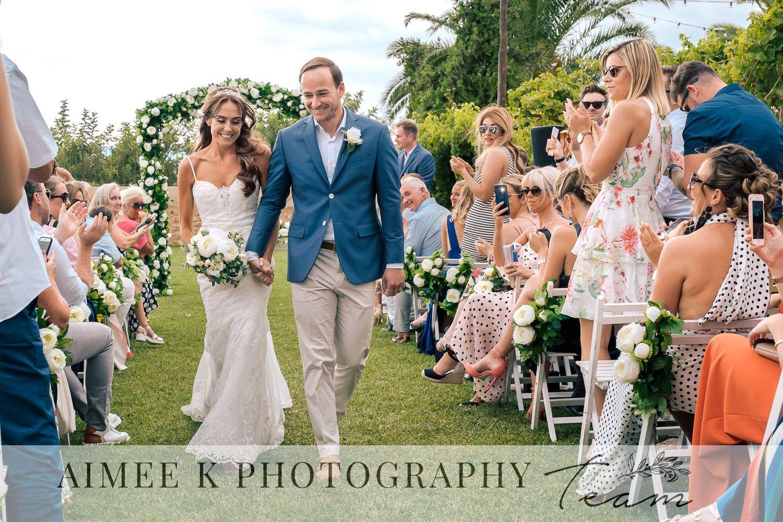 Novios sonrientes se alejan de la zona de boda tras celebración en finca de Mallorca. Invitados aplauden.