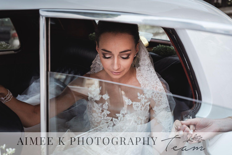 Novia vestida de blanco baja de coche para casarse