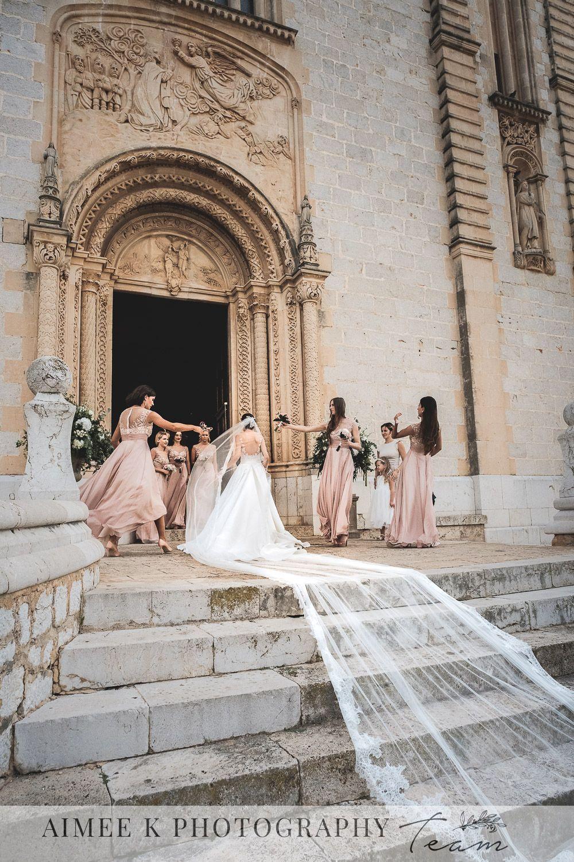 Boda en Mallorca. Novia vestida de blanco entra en iglesia. Velo largo sobre escalinata de acceso.