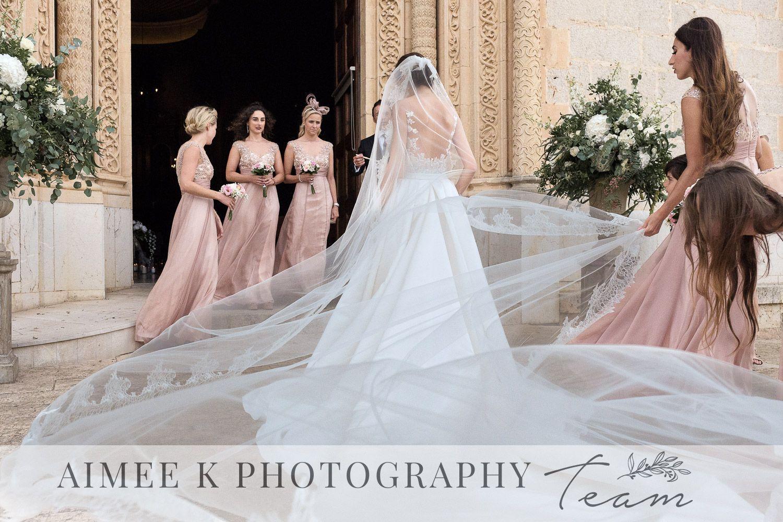 Novia vestida de blanco a punto de entrar en iglesia durante boda en Mallorca. Damas de honor ayudan y observan.
