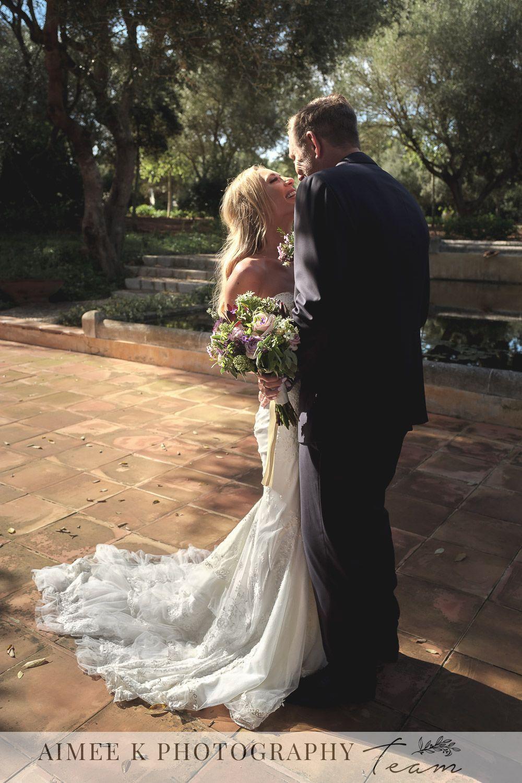 Novios sonrientes se abrazan y besan en una tarde soleada tras boda en Mallorca