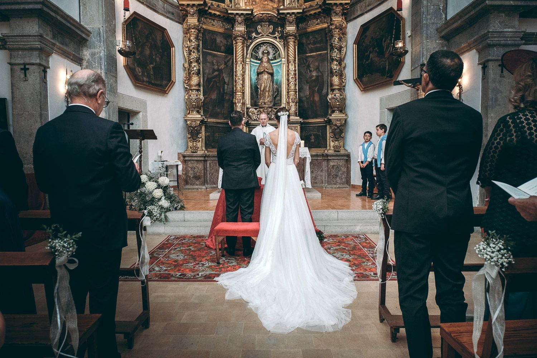 Novios en iglesia católica durante celebración de boda. Novia vestida de blanco. Velo largo. Cura. Invitados en pie.