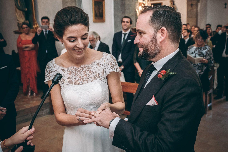 Celebración de boda en iglesia. Novia sonriente coloca el anillo de matrimonio al novio.