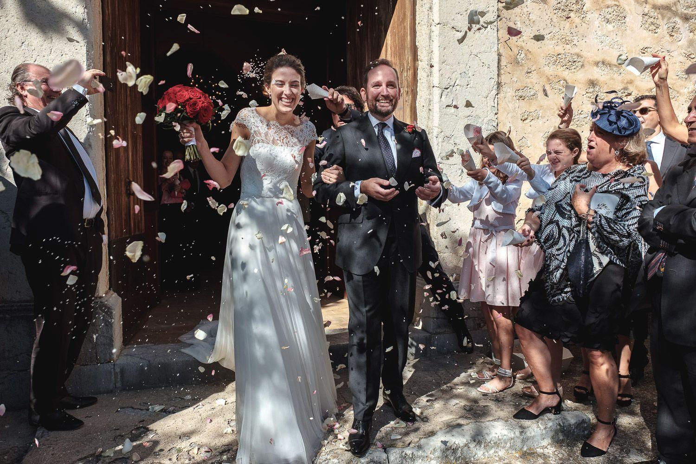 Novios sonrientes recién casados abandonan la iglesia. Invitados lanzan arroz y pétalos. Tarde soleada en Mallorca.