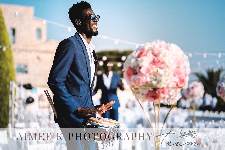 Percusionista con traje y gafas toca bongos al aire libre en boda en Mallorca. La Fortaleza