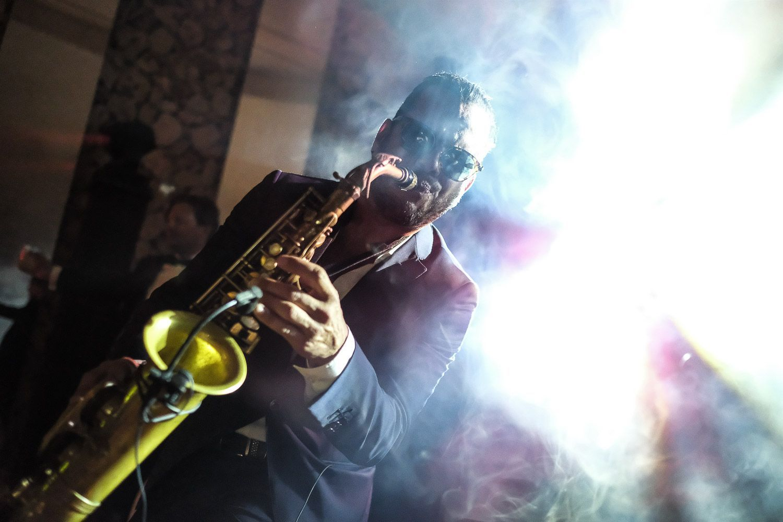 Saxofonista tocando en fiesta. Luz espectacular. Discoteca. DJ