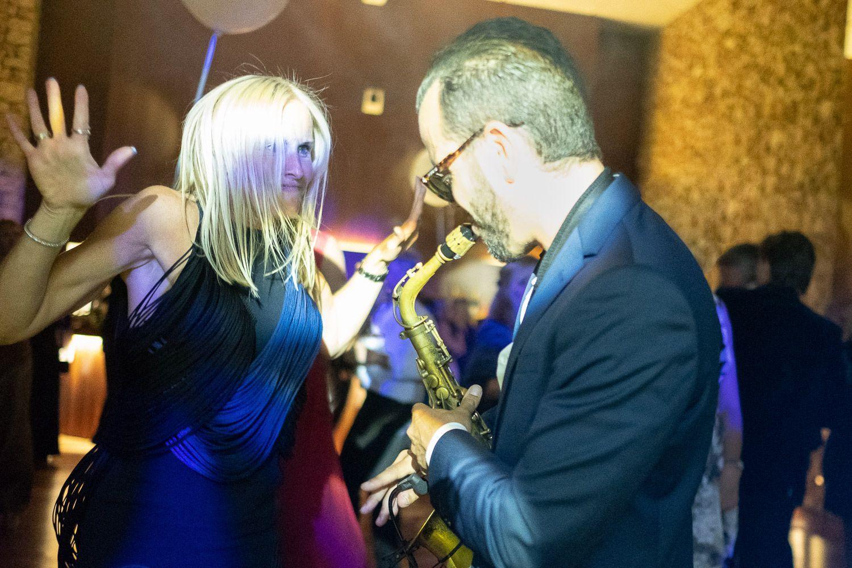 Saxofonista toca frente a mujer bailando durante fiesta