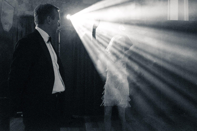Discoteca. Mujer con vestido blanco baila bajos los focos mientras hombre la observa.