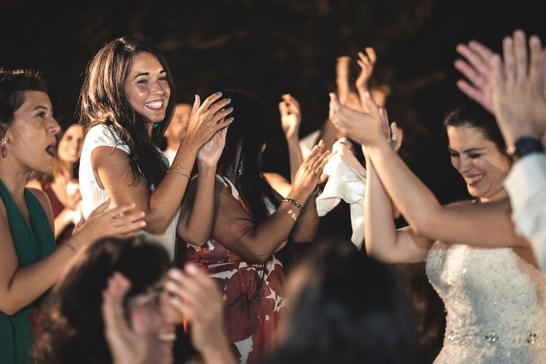 Invitadas de boda y novia en pie dando palmas. Alegría.