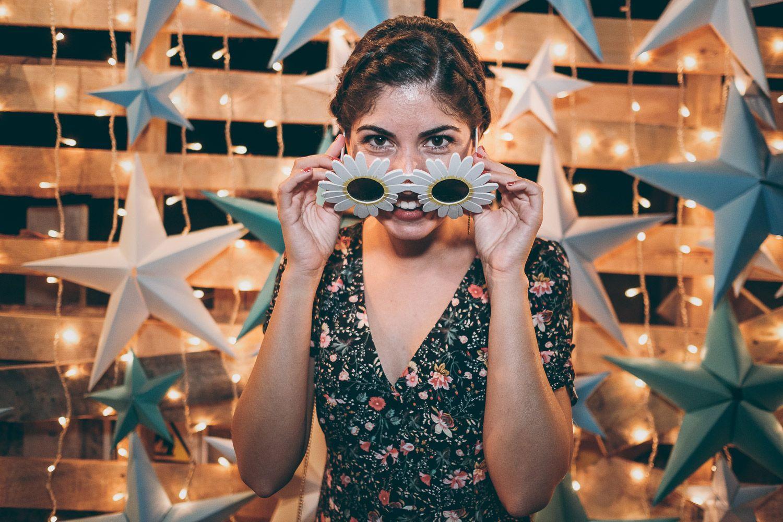 Mujer jóven sonríe mirando a la cámara con flores de margaritas. Fondo de estrellas.