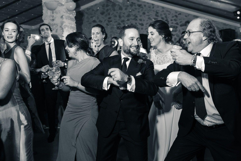 Hombres con traje y mujeres con vestido bailando en fiesta de boda. Blanco y Negro.