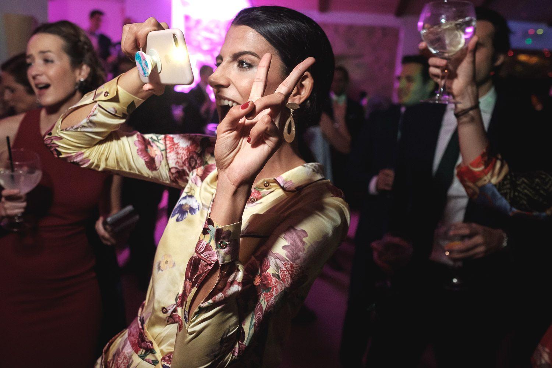 Mujer hace fotos con teléfono móvil en fiesta y hace el signo de la victoria.