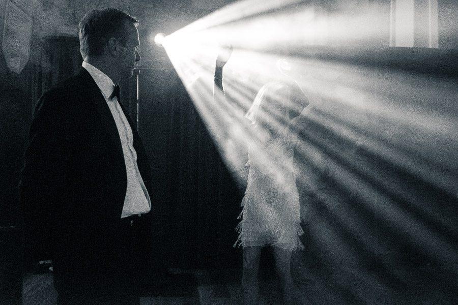 Foto en discoteca. Mujer con vestido blanco baila bajos los focos mientras hombre la observa.