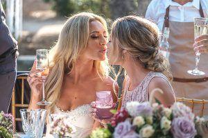 Novia y primera dama besándose durante recepción de boda.