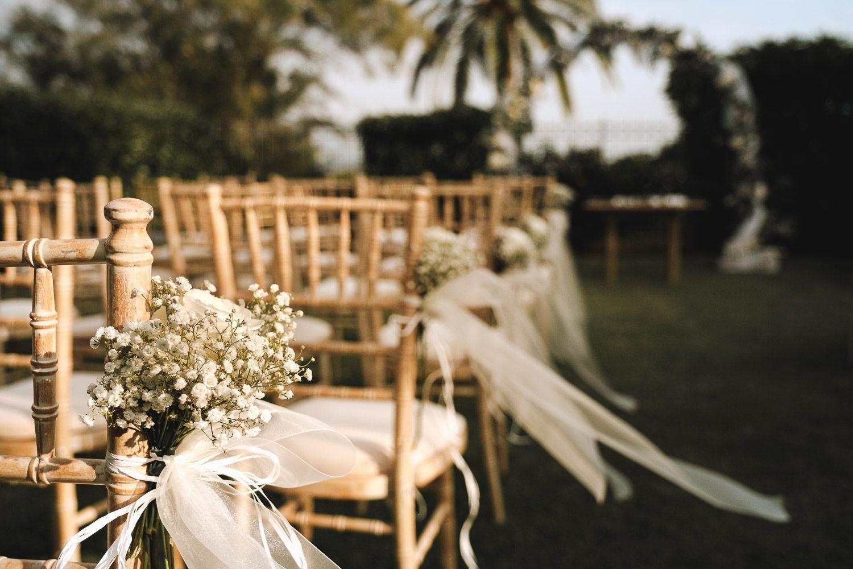 Boda al aire libre. Detalle de decoración de sillas. Flores.