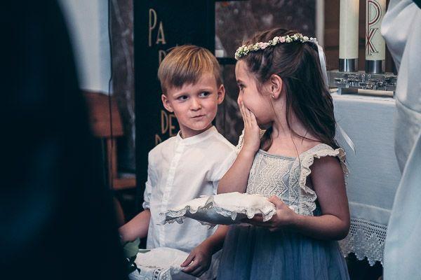 Boda en Mallorca. Niños llevando anillos y arras cuchichean en iglesia.
