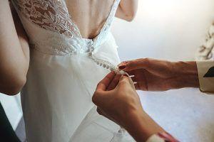 Dama de honor abrocha vestido de novia.