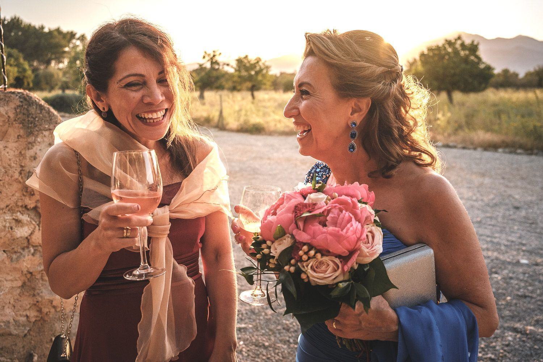 Cóctel al aire libre. Puesta de sol. Dos mujeres con copa en mano ríen.