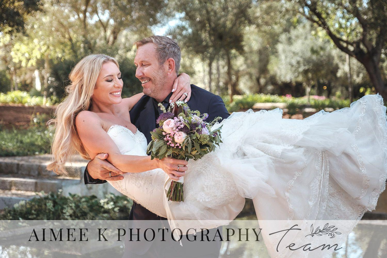 Novio lleva en brazos a novia vestida de blanco. Pareja riendo.