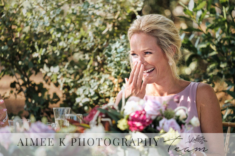 Mujer rubia invitada de boda ríe y se tapa al cara durante discurso.