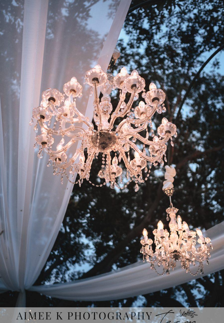 Decoración de boda al aire libre. Lámpara de araña bajo telas y árboles.