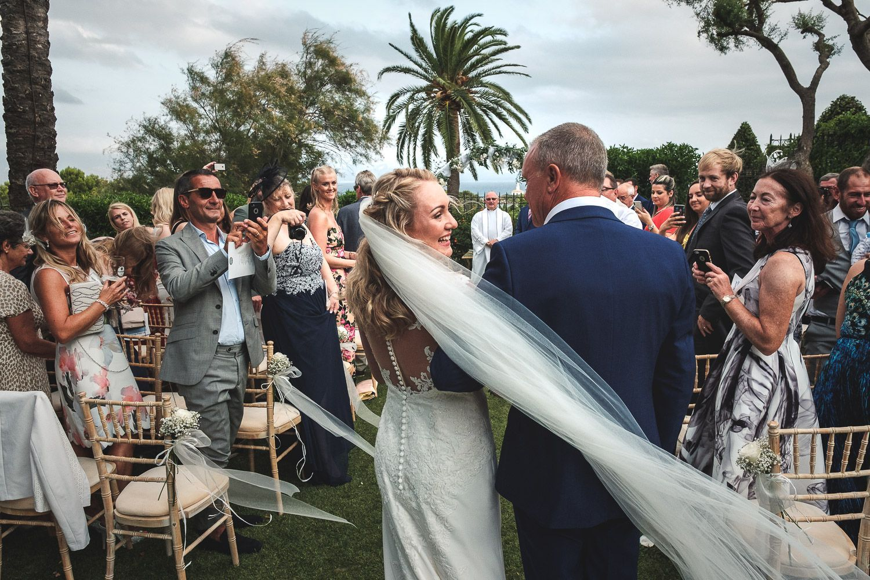 Entrada de la novia acompañada de su padre. Ceremonia al aire libre.