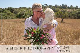 Matrimonio se besa en campo de cereal. Renovación de votos. Bodas de oro. Flores. Días soleado.