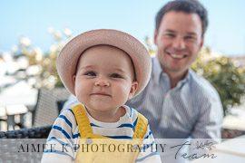 Niña pequeña con papá miran a la cámara sonrientes